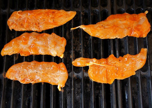 Raw chicken cooking on a grill