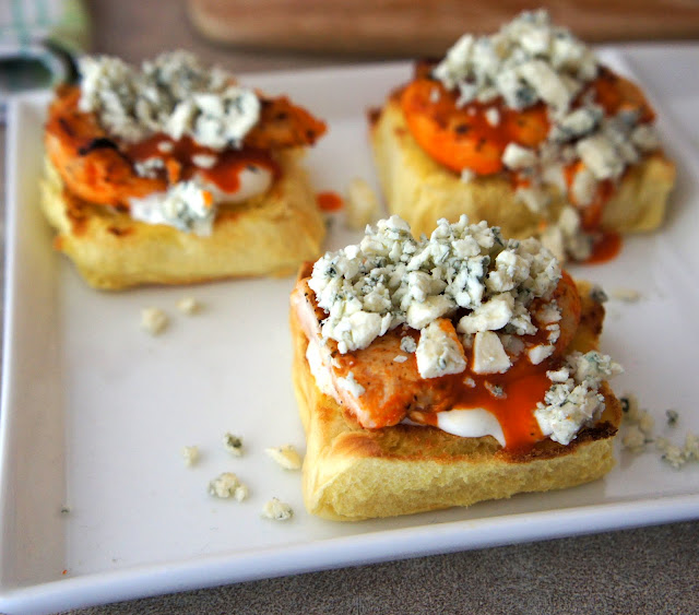 A plate with three slider halves, each topped with white sauce, chicken, red sauce and blue cheese