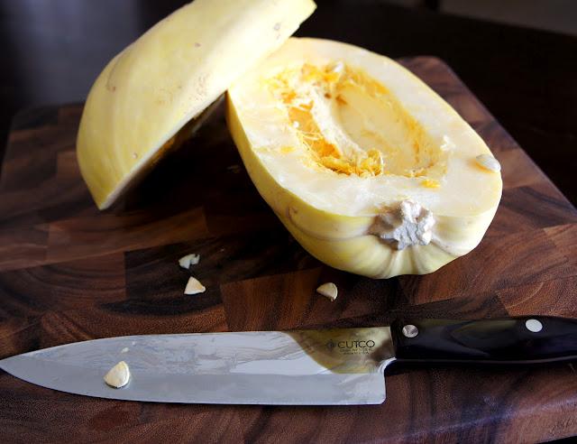 A spaghetti squash cut in half on a cutting board