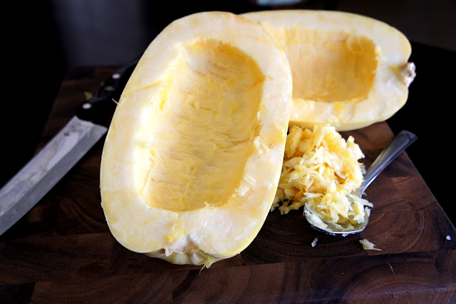 A spaghetti squash cut in half with no seeds in the centers and a pile of seeds next to them on the cutting board