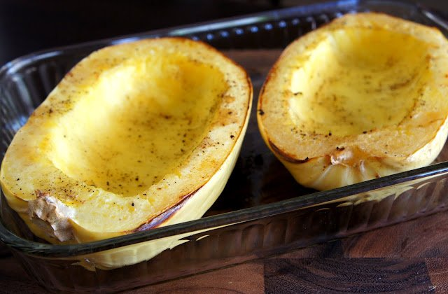 Two halves of baked spaghetti squash in a pan
