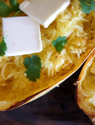 A close up of baked spaghetti squash with a couple squares of melting butter and herbs on it.