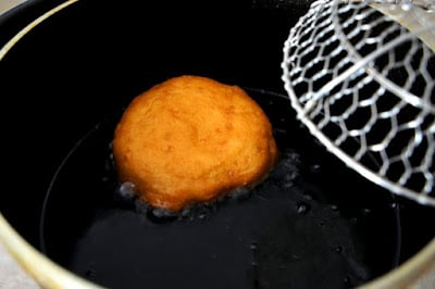 A close up of a fried biscuit in a pan of oil