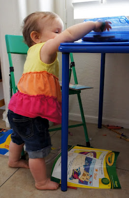 A little girl standing next to a kid table with her hand reaching onto a plate