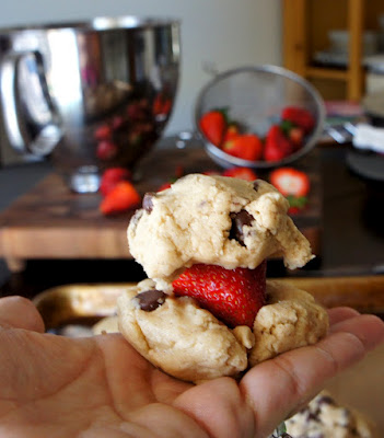 A hand holding a strawberry between two small balls of raw cookie dough
