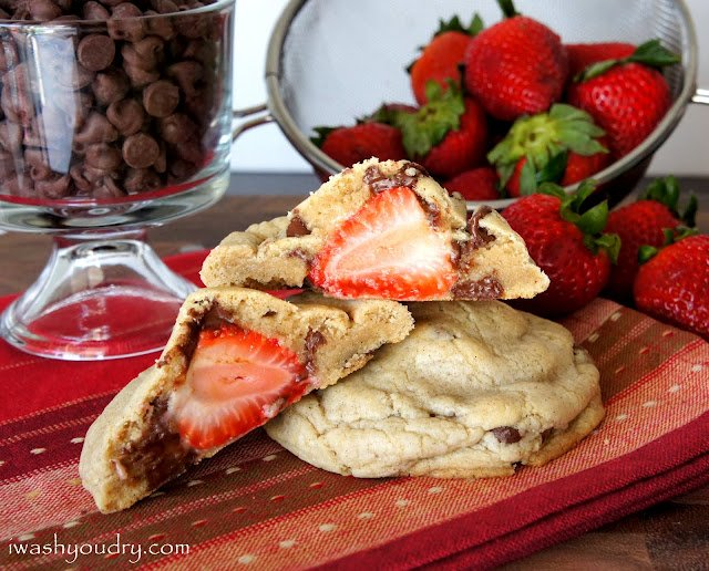 A display of a baked cookie cut open to show the whole strawberry stuffed inside