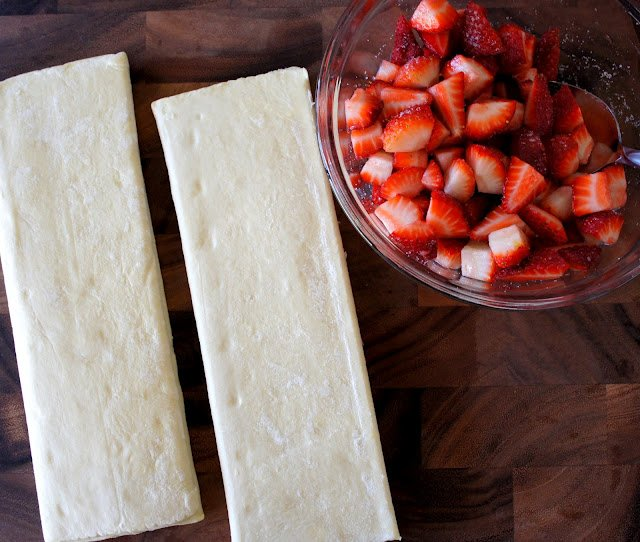 A bowl of cut up strawberries next to long strips of raw dough laid out on a table