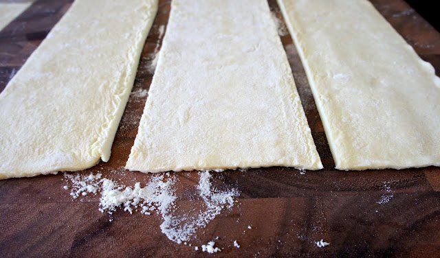 A close up of strips of raw dough on a floured cutting board