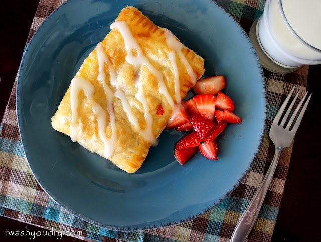 A Strudel on a blue plate with a side of diced strawberries