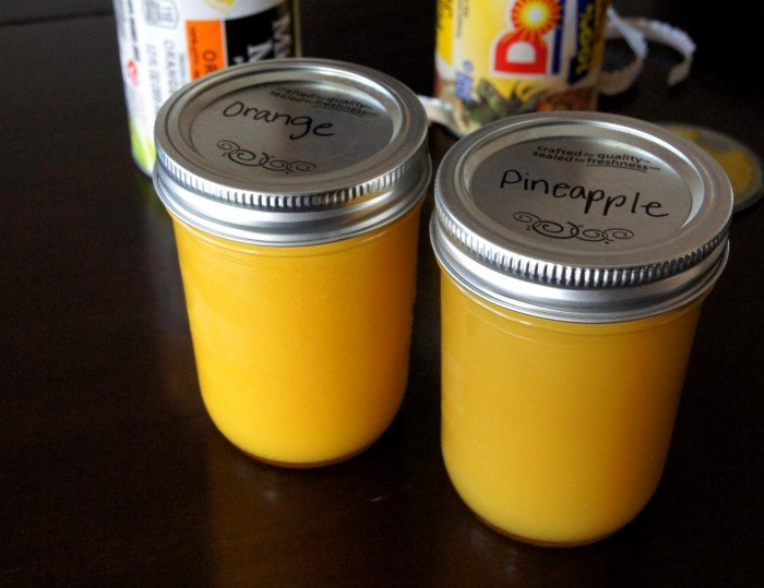 """Two Mason jars with lids on a table with one labeled \""""orange\"""" on one lid and the other \""""pineapple\"""" on the lid"""