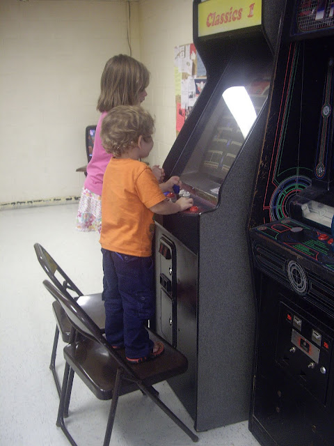 A boy and girl playing arcade games.