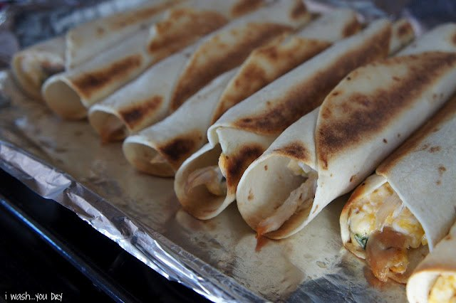 A close up of a baking pan with baked flautas on it.