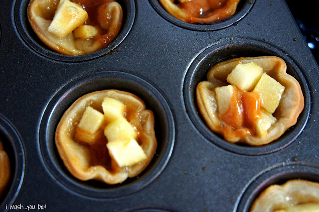 A close up look of baked chopped apples in mini pie crusts in a muffin tin.