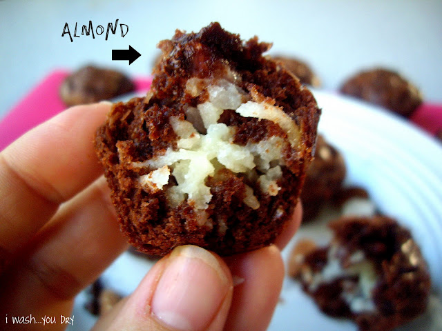 A hand holding a brownie muffin cut open to show the coconut and almond inside.