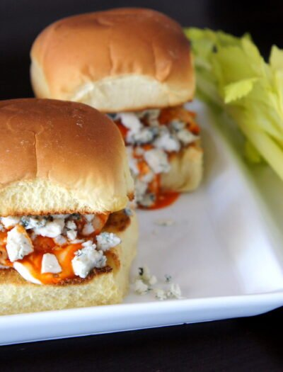 A close up of a plate of sliders filled with buffalo chicken and blue cheese