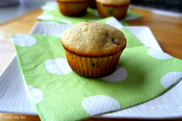 A close up of a baked muffin on a green polka dot napkin.