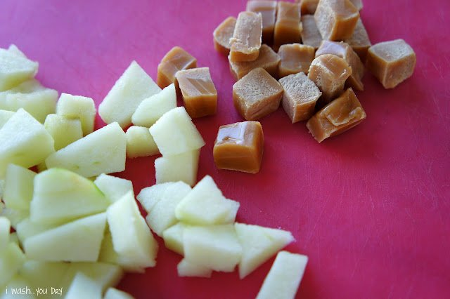 Close up of chopped apples next to chopped caramel squares on a cutting board.