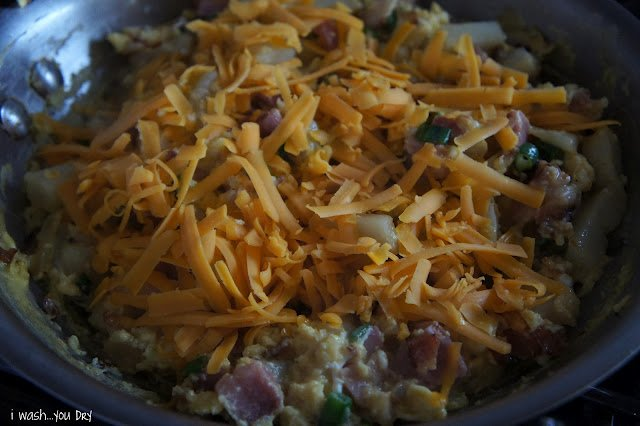 Close up of a pan of cooked food with shredded cheddar cheese on top.