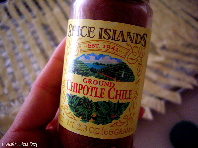 A hadn\'t holding a bottle of Ground Chipotle Chile
