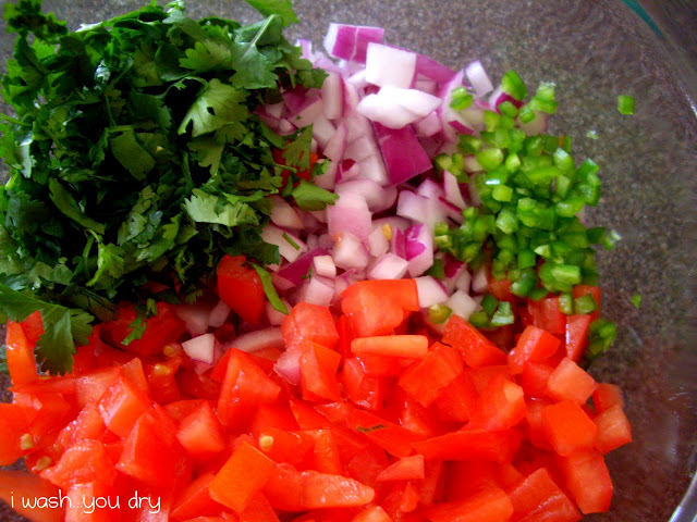 Chopped cilantro, onions, serrano pepper and tomatoes on a cutting board.
