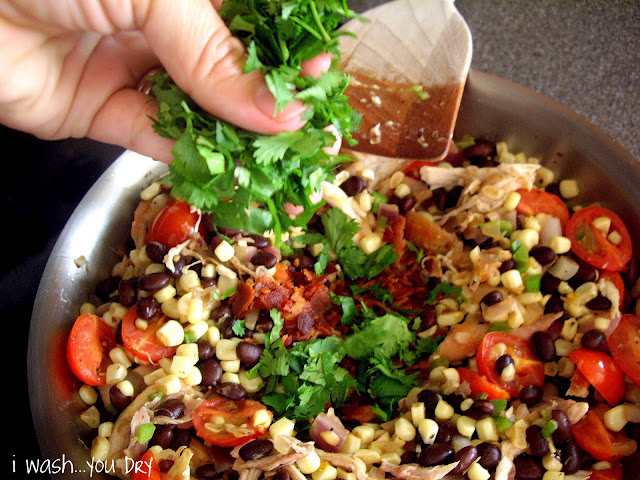 A hand adding chopped cilantro to a mixture of shredded chicken, corn, black beans and tomatoes in pan.