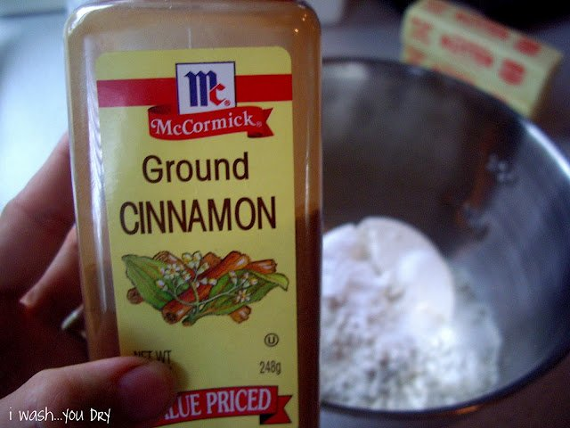 A hand holding a bottle of Ground Cinnamon in front of a mixing bowl.