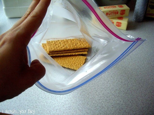 A hand holding open a ziplock bag filled with graham crackers.