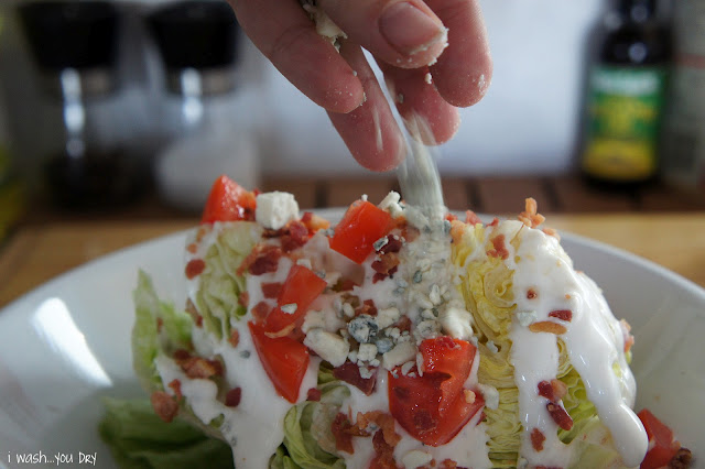A hand adding blue cheese onto the top of a salad.
