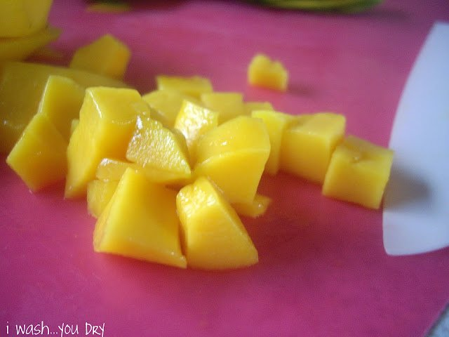 Cubbed mango pieces on a cutting board.