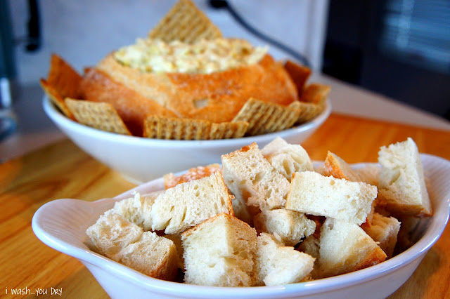 A bowl of chopped bread in front of a round loaf of bread with dip in it.