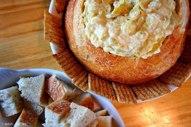 A close up of a display of a bread bowl with a dip inside of it, lined with crackers and next to a bowl of chopped bread.