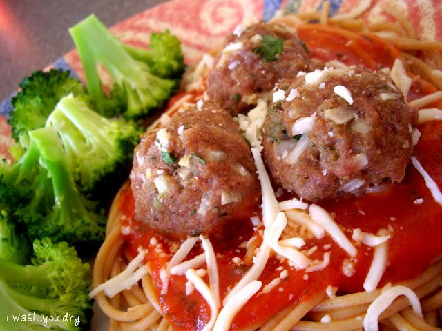A close up of a plate of food with broccoli, meatballs and pasta.
