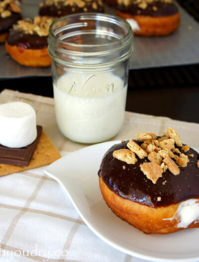 A Marshmallow Cream filled S'mores Doughnut displayed on a plate next to a glass of milk and an uncooked S'more