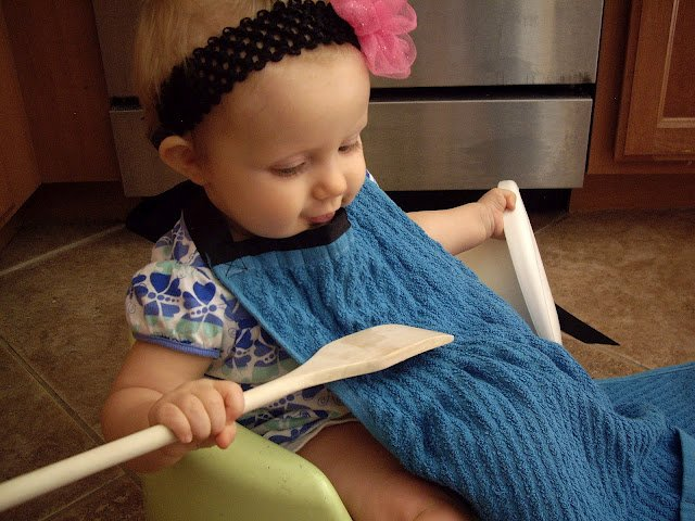 A baby in a baby chair wearing a dish towel apron