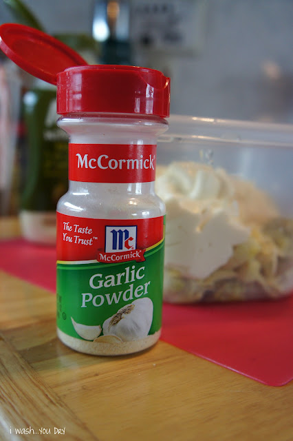 A close up of a bottle of Garlic Powder in front of a plastic bowl of dip ingredients.