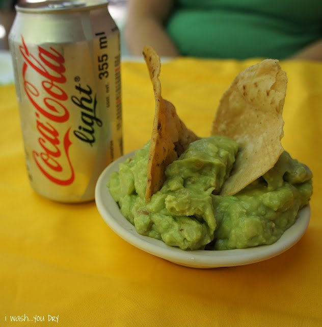 A can of Cocoa Cola Light next to a bowl of guacamole with two chips in it.