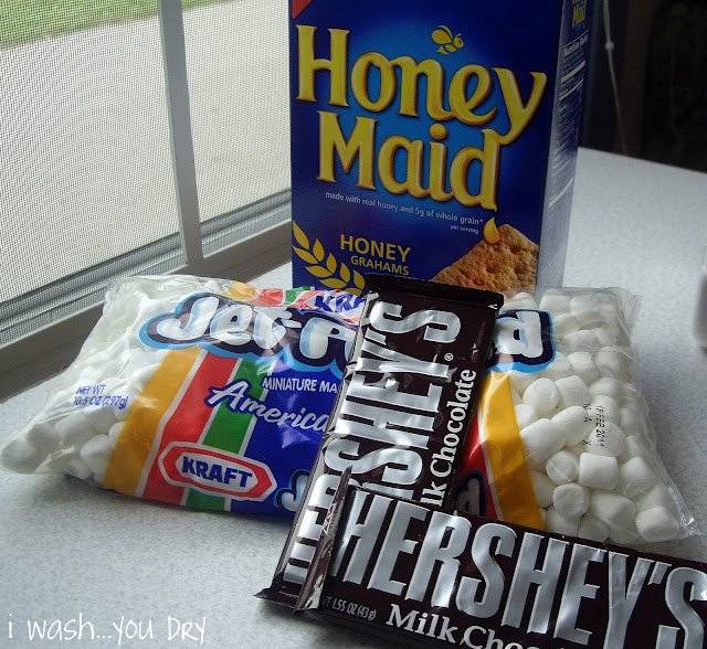 A large box of graham crackers, a bag of marshmallows and two milk chocolate candy bars.