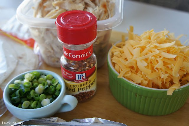A display of needed ingredients to make Pllo Fundido Flautas; shredded chicken, crushed red peppers, cheese and green onions.