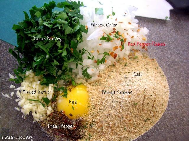 A display of needed ingredients to make Turkey meatballs: Parsley, garlic, pepper, egg, salt, bread crumbs, onion.