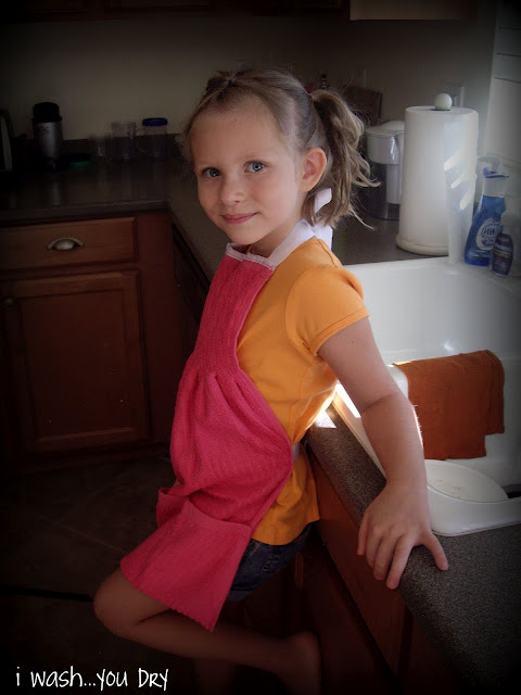 A little girl wearing a dish towel apron.