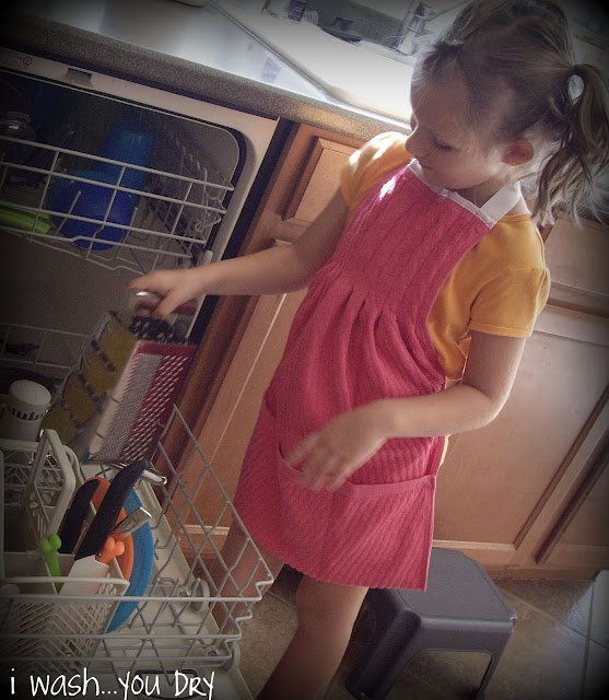 A little girl emptying the dishwasher wearing a dish towel apron.