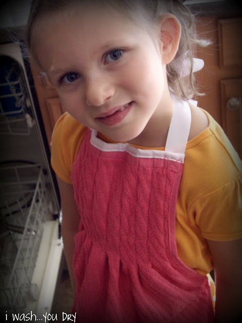 A close up of a little girl wearing a dish towel apron.