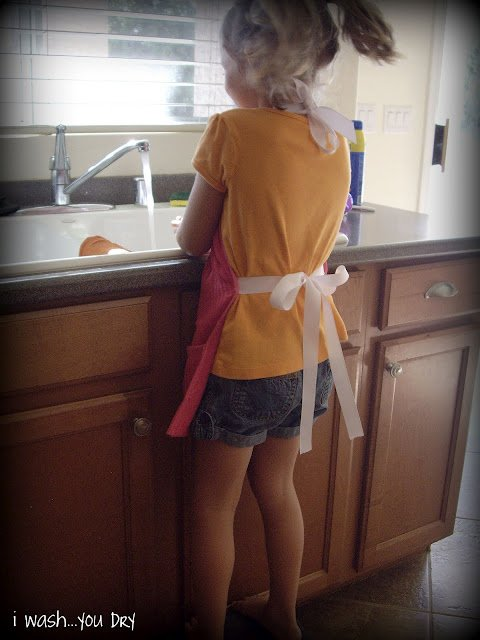A girl wearing an apron standing at the kitchen sink washing dishes.