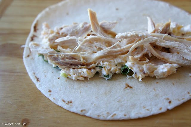 A display of a flour tortilla with a creamy veggie layer topped with shredded chicken.
