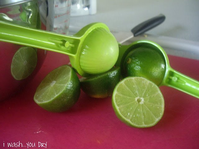 Lime halves on a cutting board next to a lime juicer.