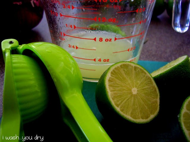 Half a lime in front of a clear measuring cup with lime juice in it.