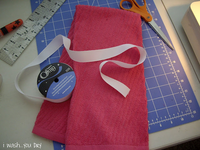 A display of needed items to make a dish towel apron: dish towel, scissors, ribbon.