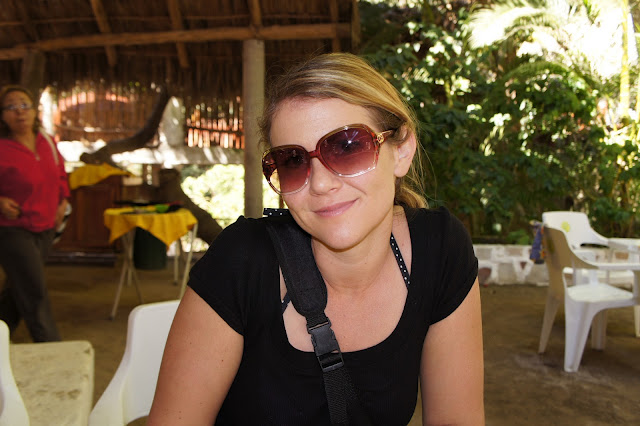 A woman in sunglasses sitting in a restaurant.