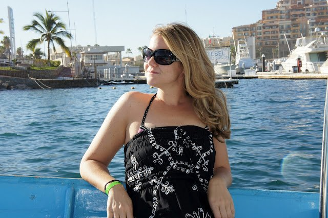 A woman with sunglasses on standing in front of a body of water