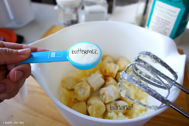 Buttermilk being added to a mixing bowl with sliced bananas in it.